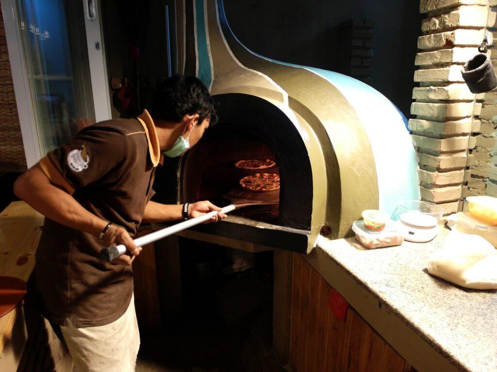 Adonan pizza tungku dimasukkan ke dalam tungku pemanggang kayu bakar - Coffe n' Friends
