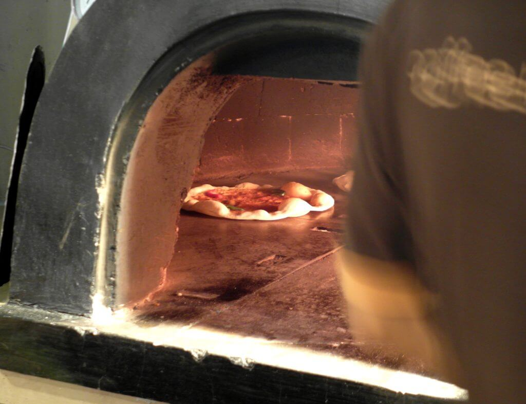Pizza tungku di dalam tungku pemanggang kayu bakar hampir matang - Coffe n' Friends